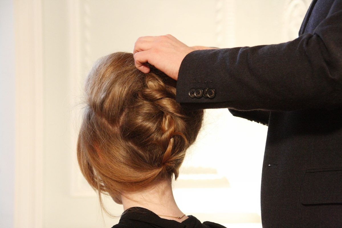 This is a woman whose hair is being put up in a reverse braid.