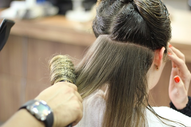 this is a woman getting her hair brushed with a roller brush.