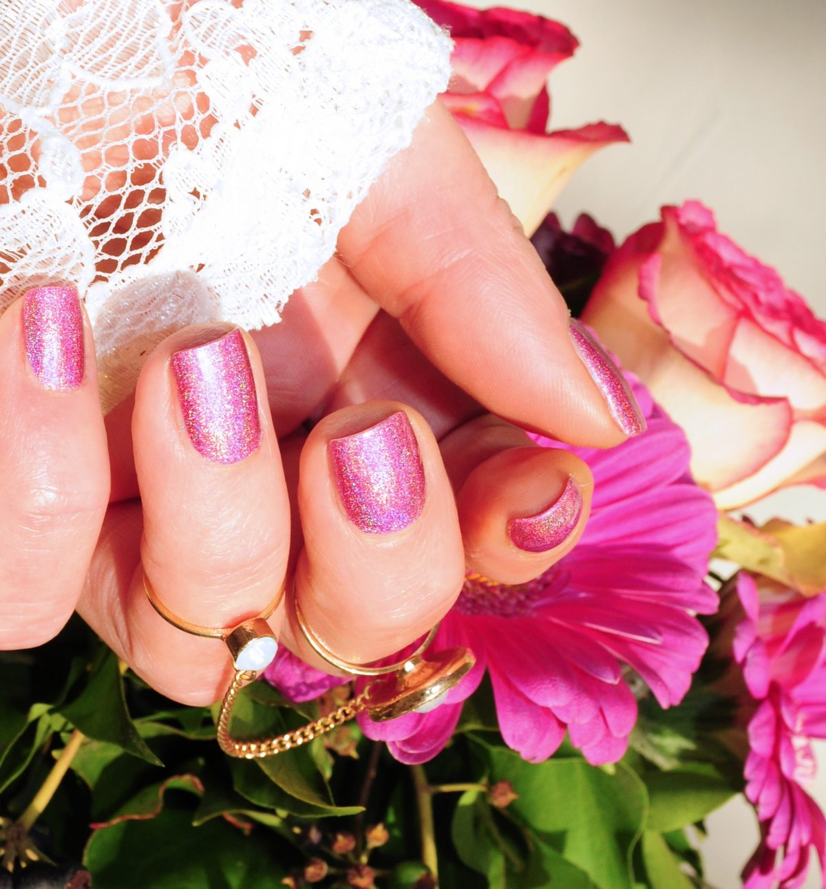 These are sparkly pink nails and a bouquet of pink and white flowers.